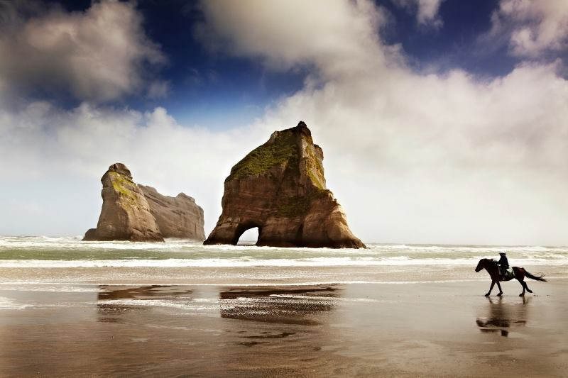 www.lacavalieremasquee.com | Rider on horseback on Wharariki Beach at Cape Farewell, South Island by Matt Munro / Lonely Planet Traveller Magazine